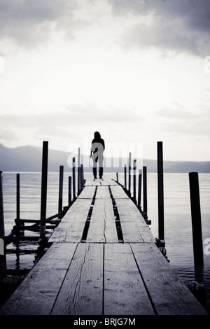 Chica en pie al final de un muelle en el lago mirando hacia fuera.