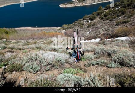 Un joven cambia de telemark botas zapatos para la última parte de la ruta, durante una excursión de esquí de primavera en junio de lago, Calif