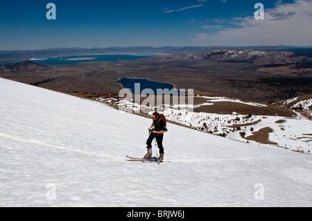 Durante su última excursión de esquí durante la temporada, un joven pieles arriba en la montaña con el Lago Mono en el fondo, en junio de lago, Calif