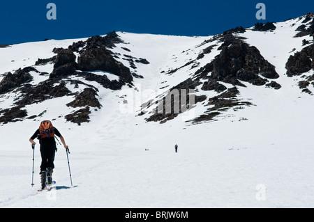 Durante su última excursión de esquí durante la temporada, un joven pieles para la cumbre en junio de Lake, California.
