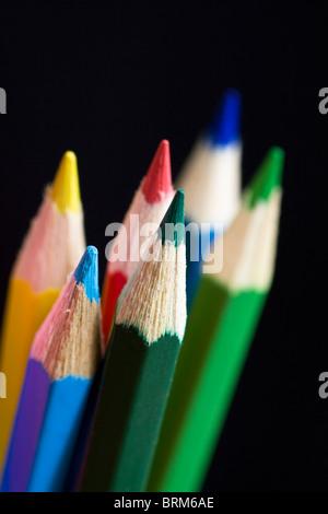 Lápices de colores sobre fondo negro. El enfoque selectivo.