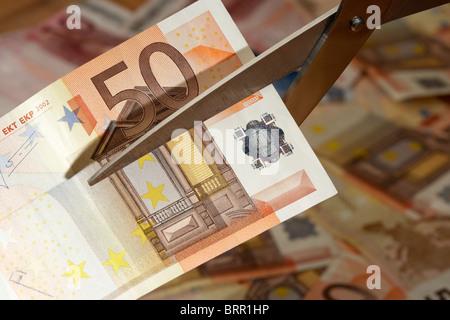 Montón de cincuenta billetes con 50 euros nota ser cortada con un par de tijeras en Europa eurozona Foto de stock