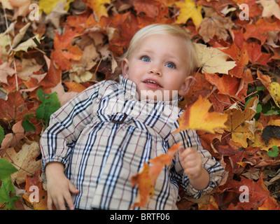 Dos años de edad, niña acostada en árbol caído hojas en el otoño la naturaleza