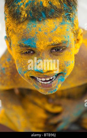 Feliz joven niño indio cubierto de polvo coloreado. La India