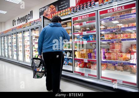 Un hombre en busca de un tema en la sección de congelados del supermercado de Co-Op, REINO UNIDO Foto de stock