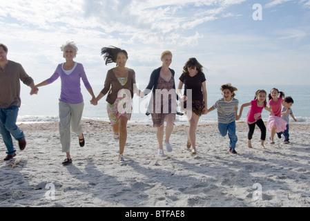 Grupo de personas sosteniendo las manos y girando en la playa