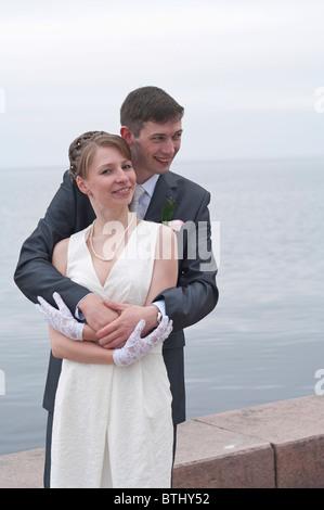 Hermosa joven recién casada pareja caminando por el muelle de Petrozavodsk, Rusia. Abrazándose entre otros