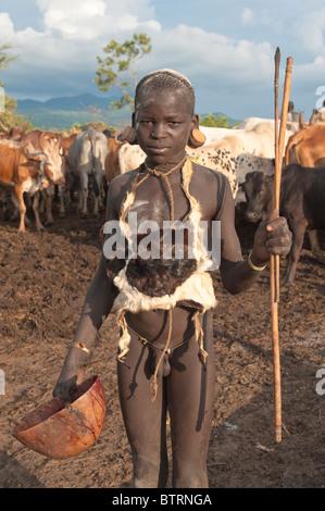 Surma boy en un campamento cerca de ganado Tulgit, Valle del río Omo, Etiopía