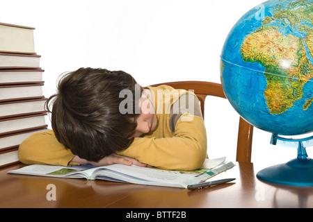 Cansado niño durmiendo mientras haciendo los deberes