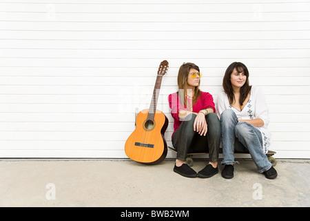 Dos niñas sentados en el suelo con la guitarra