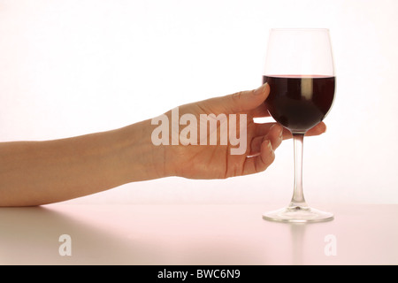 Mano que alcanza para un vaso de vino tinto (tonos magenta)