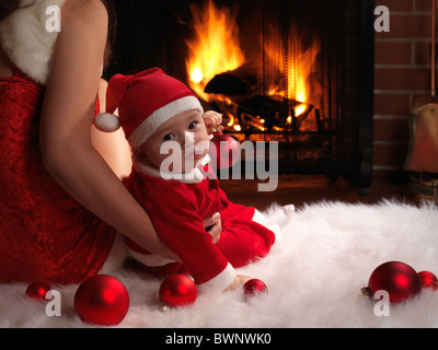 Madre y un poco de Baby Boy sentado delante de una chimenea en trajes de Navidad.