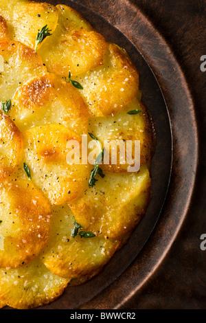 Tortas de patata o Anna aderezado con tomillo fresco, sal y pimienta y se sirve en un plato rústico.