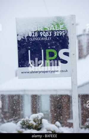 Los agentes inmobiliarios firmar recubiertas de nieve en inviernos fríos con nieve día en Belfast, Irlanda del Norte