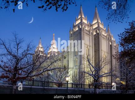 Las primeras horas de la noche con una luna creciente sobre el Templo Mormón en el centro de Salt Lake City, Utah en invierno