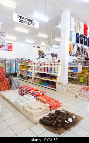 Interior de un supermercado en un país en desarrollo, con arroz y hortalizas de raíz en el suelo. Foto de stock