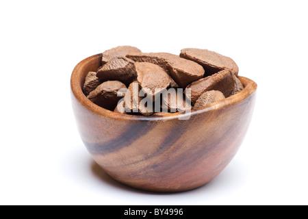 Las nueces de Brasil en un recipiente de madera sobre fondo blanco.