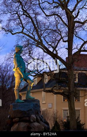 El atardecer en el Minuteman estatua con Buckman Tavern más allá de Lexington, Massachusetts, EE.UU.