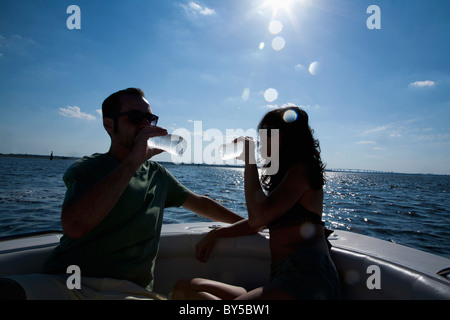 Una pareja en su barco beber agua embotellada