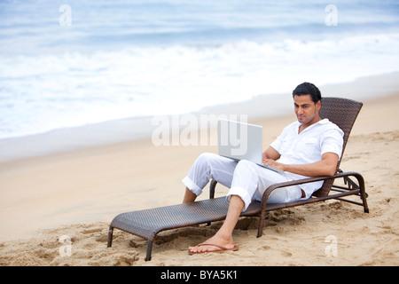 Hombre con un portátil en una playa Foto de stock