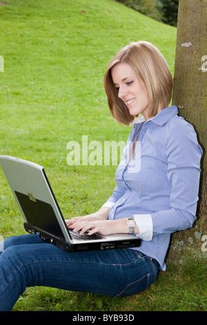 Joven Mujer rubia sentada en el parque en el césped y trabajando en un portátil.
