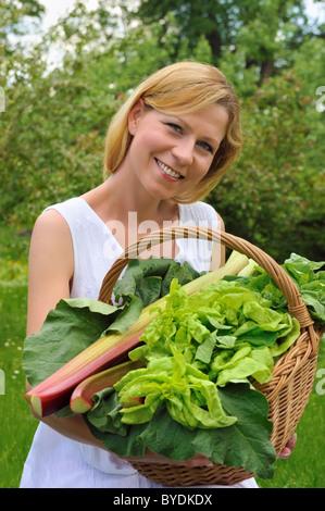 Mujer joven sosteniendo una cesta con verduras