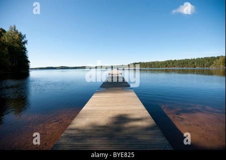 Embarcadero de madera conduce hacia un gran lago, Suecia, Europa