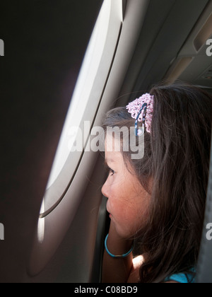 Niño en un avión, mirando por la ventana