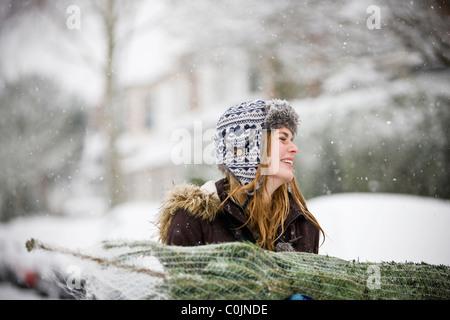 Una joven mujer que llevaba a un árbol de Navidad en la nieve.