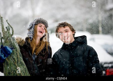 Una joven pareja con un árbol de Navidad en la nieve, riendo