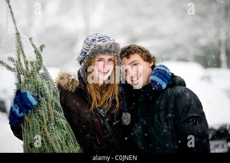 Una joven pareja con un árbol de Navidad en la nieve.