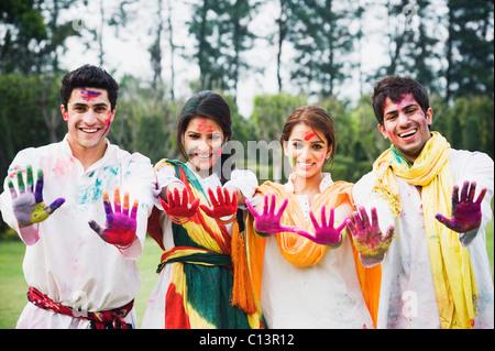 Amigos mostrando sus manos de colores mientras se celebra Holi Foto de stock