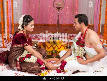 Pareja de recién casados jugando Kangana Jua durante la ceremonia de boda del sur de la India Foto de stock