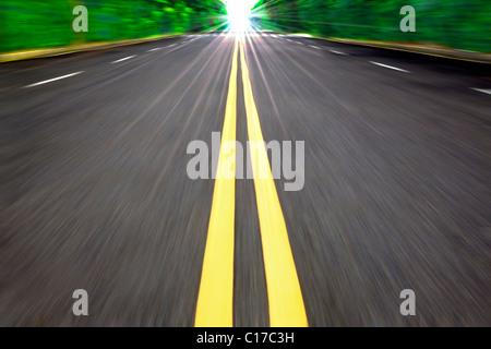 Coche de conducción de alta velocidad en la carretera vacía