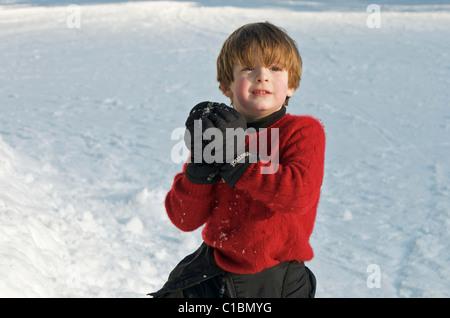 Jengibre pelo lindo chico listo para lanzar una bola de nieve en un día de invierno