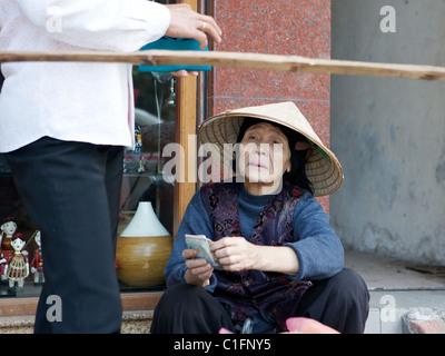 Retrato de la calle vieja en un sombrero cónico de la tradicional no en Hanoi, Vietnam
