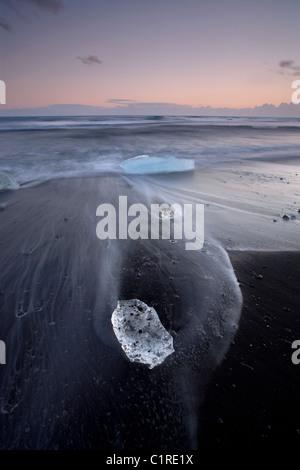 Los icebergs en playa negra con la marea lavado alrededor de ellos en Islandia Foto de stock