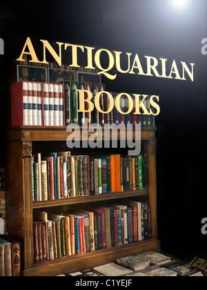 Librería Anticuaria ventana con signo y antiguos libros y librería en la pantalla con el sol quema el cristal de Foto de stock