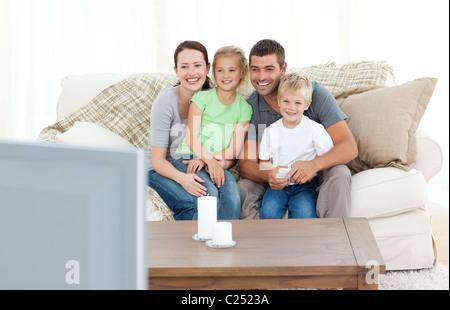 Adorable familia juntos viendo la televisión sentado en el sofá