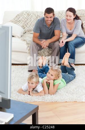 Adorable hermanos viendo televisión con sus padres yacían en el suelo