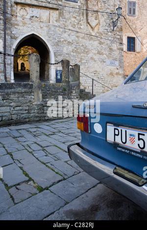 Viejo coche delante de la antigua puerta de la ciudad de Motovun, Istria, Croacia