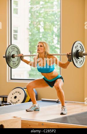 Una mujer físicamente apto hacer sentadillas en un club de la salud sala de pesas.