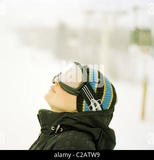 Mujer vistiendo gafas de esquí mirando hacia arriba