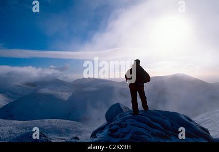 Walker en invierno la cumbre de Slieve Bearnagh, las Montañas Mourne, Condado de Down, Irlanda del Norte.