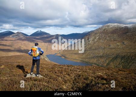 Walker mirando a lo largo del valle desde Slievenaglogh silenciosa, las Montañas Mourne, Condado de Down, Irlanda del Norte.