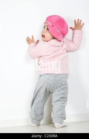 Atrás de todo el cuerpo de una niña de 11 meses de edad de pie con las manos en la pared y apartar la mirada por encima del hombro