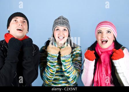 Feliz tres amigos en ropa de invierno aclamaciones y mirando sorprendido .Puede agregar en esa imagen regalos,regalos,dinero