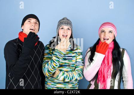 Sorprendidos y felices amigos mirando hacia arriba a copiar el espacio y tener una sorpresa y manteniendo sus manos a la boca
