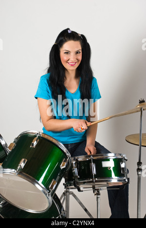 Mujer joven baterista reproducir música en drum set
