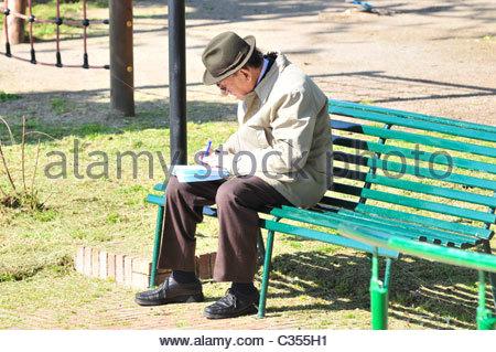 Anciano sentado en un banco Foto de stock
